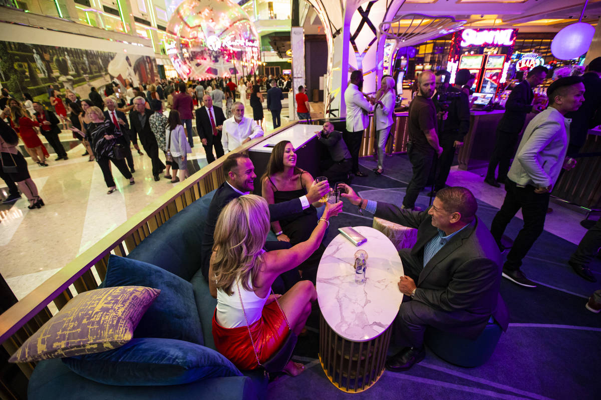 People toast and mingle at Gatsby's cocktail lounge during the opening night of Resorts World L ...